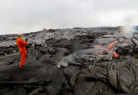 Despite heavy rain, which resulted in blurry spots on this photo due to water droplets on the camera lens, HVO scientists were able to do some of the work they hoped to accomplish during this morning's overflight. Here, an HVO geologist maps the location of active lava from the eastern breakout on Puʻu ʻŌʻō. Photo taken Wednesday, May 25, 2016 courtesy of USGS/HVO