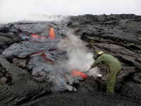 Amidst steam created by rain falling on the hot lava, another HVO geologist uses a rock hammer to collect a sample of the active flow. Analyses of this sample will yield data on the temperature and chemical makeup of the lava, information that is needed to help determine what's happening within the volcano. Photo taken Wednesday, May 25, 2016 courtesy of USGS/HVO