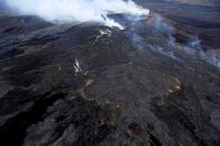 This photo, looking southwest, shows Puʻu ʻŌʻō in the background, with the northern breakout from May 24 extending to the right, with fume coming from a newly forming tube. The feature in the center foreground is a perched lava pond that formed in July 2014, but was refilled by new lava from the northern breakout in recent days. The breakout point of the eastern breakout is hard to pick out, if you don't know what to look for. It's the lighter colored lava at the left edge of the photo immediately below center. Photo taken Thursday, June 2, 2016 courtesy of USGS/HVO