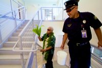 Kahu Isaia Kealoha walks through the new Hilo International Airport Aircraft Rescue and Firefighting Station sprinkling holy water with ti leaf to bless the facility. Photography by Baron Sekiya | Hawaii 24/7