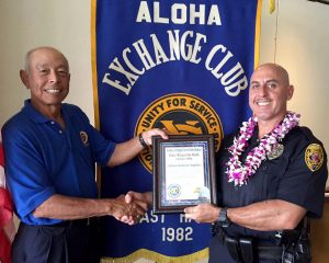 Aloha Exchange board member Joey Estrella presents an 'Officer of the Month' award to Officer Roberto Segobia.