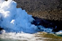 A close-up view of the Kamokuna ocean entry. A tiny delta has been building, but is not clearly visible through the thick plume. One spot of incandescence can be seen through a break in the plume (center) just above sea level. Floating, steaming blocks were also seen in the water just off the ocean entry (lower middle-right). Photo taken Thursday, March 30, 2017 courtesy of USGS/HVO
