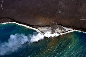 An aerial view of the Kamokuna lava delta reveals the recent surface breakouts (dark flows) that began on Sunday, June 25, with the short-lived firehose activity. These flows contrast nicely with the older, altered delta surface, which is much lighter in color. The crack noted in our June 22 images is clearly visible on the western (left) side of the delta in today's photo, and is a good reminder of delta instability. Photo taken Thursday, June 29, 2017 courtesy of USGS/HVO