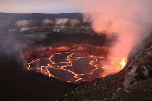 The lava lake within Halemaʻumaʻu at the summit of Kīlauea illuminated the vent walls on the evening of February 13, 2017. Circulation within the lava lake causes upwelling and down-welling on opposite sides of the lake. This often results in spattering on the lake surface (right), which creates bright spots on the dark, semi-solid lake crust. Circulation can also pull sections of the crust apart, exposing the molten lava beneath and creating incandescent lines on the lake surface. USGS photo, M. Patrick
