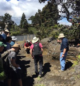 USGS geologist Don Swanson (right) explains Keanakāko'i Tephra stratigraphy exposed near the Hawaiian Volcano Observatory to scientists who visited Kīlauea during a Geological Society of America field trip in May 2017. USGS photo by T. Neal.