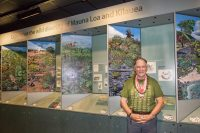 Dave Parker poses for a photo in front of an interpretive display in the Kīlauea Visitor Center of Hawai'i Volcanoes National Park. NPS Photo by Janice Wei