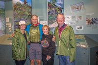 Left to right: Sheri Cavaney, Dave Parker, Carol Parker and Red Cavaney, smile for photos in the Kīlauea Visitor Center on Wednesday. Dave is wearing an NPS Centennial T-shirt listing all 59 national parks. NPS Photo by Janice Wei