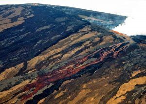 Aerial view of Mauna Loa erupting on the morning of March 25, 1984, the first day of the volcano's most recent eruption. The lava flow was advancing southeast, toward Kīlauea, from fissure vents at an elevation of about 11,200 feet on Mauna Loa's Northeast Rift Zone. Moku'āweoweo, Mauna Loa's summit caldera, is visible at top left. USGS photo by J.P. Lockwood.