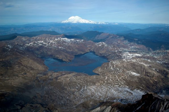 Aerial view of Spirit Lake (center) looking north from above the crater of Mount St. Helens. The lake's outlet to the west (left) was blocked by the 1980 landslide, which required a new engineered outlet to maintain the lake at a safe level. A tunnel was drilled through a bedrock ridge on west side of lake in 1984-1985. Glacier covered Mount Rainier in distance. USGS photo by M. Logan, 2005.