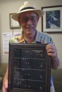 Ron Thiel and a photo of an asteroid named after him. Photo courtesy Hawaii County Mayor's Office