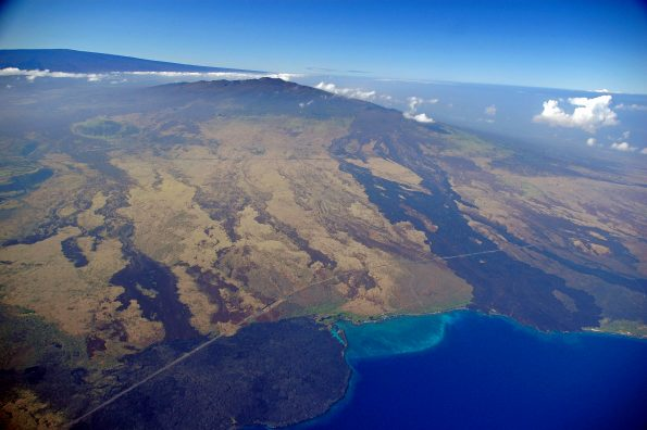 """Hualālai (center) and Mauna Loa (left background), two of the four active volcanoes on the Island of Hawaiʻi, are ranked as """"high threat"""" and """"very high threat"""" volcanoes, respectively. Kīholo Bay (right foreground) is flanked on the north (left) by a lava flow erupted from Mauna Loa in 1859 and on the south by the Ka'ūpūlehu flow erupted from Hualālai around 1800.  Photo courtesy of USDA Forest Service."""