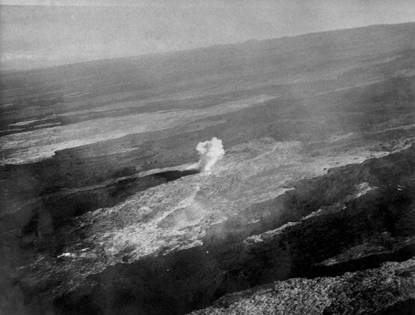 Aerial view of a bomb detonating on Mauna Loa near the 8500-foot elevation source of the 1935 lava flow on the morning of December 27, 1935. This was one of twenty 600-pound bombs dropped on the lava flow that morning by the Army Bombing Squadron from Luke Field, O'ahu. Photo by Army Air Corps, 11th Photo Section.