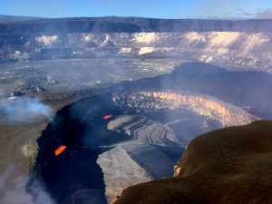 """On January 8, 2018, Kīlauea Volcano's summit lava lake level was 38 m (125 ft) below the rim of """"Overlook crater,"""" the small crater that formed above the active vent in Halemaʻumaʻu. The lava lake continuously emits elevated levels of sulfur dioxide gas and erupts small, but measurable, amounts of Pele's hair and other ash-sized tephra (airborne lava fragments) that accumulate on the rim of Halemaʻumaʻu (lower right) and areas downwind of the lake. USGS photo by J. Sutton."""