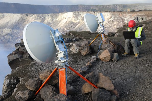 Dr. Nial Peters from the University of Cambridge sets up the prototype radar on the rim of Halema'uma'u at the summit of Kīlauea in January 2018. Microwave pulses are transmitted from one dish towards the lava lake surface. Some of the microwave energy is reflected back and is received by the other dish. The range or distance to the lava lake is then calculated from the time taken between transmission and reception of the pulses, providing a sensitive measure of the lava lake height. Measurements can be made continuously. Photo courtesy of C. Oppenheimer.