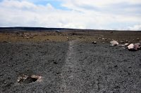 Viewing the Halema'uma'u parking lot (in background) from within the area of the explosive deposit. There is a clear boundary where the new deposit (which is gray in color) ends, and the blanket of Pele's hair (golden brown) continues. Photo taken Friday, April 6, 2018 courtesy of U.S. Geological Survey
