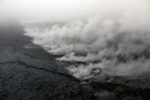 A new crack 1 km (0.6 mile) long was found on the west (uprift) side of Pu'u 'Ō'ō during HVO's overflight today. The cracking appeared to be nearly continuous en echelon structures that were heavily steaming. A small amount of lava was apparently erupted from the crack, based on the presence of nearby tiny pads of lava and spatter, but it was no longer active when HVO geologists saw it during the overflight. This photo looks east, with Pu'u 'Ō'ō obscured by low clouds in the upper left corner. Photo taken Tuesday, May 1, 2018 courtesy of U.S. Geological Survey