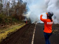 At 13:00 p.m. HST. A new fissure extended across Pohoiki Road between the intersections of Leilani Avenue and Hinalo Street. Scientists had difficulty viewing the entire fissure from their location, but reported lava spatter 5 m (7 ft) high as well as a loud jetting of gas from the fissure. This photo shows the steaming fissure extending across Pohoiki Road. Photo taken Wednesday, May 9, 2018 courtesy of U.S. Geological Survey