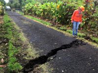 At 1:54 p.m., HST. Geologist inspects a crack that widened considerably in the past day on Old Kalapana Road. In other areas, new cracks have appeared along sections of Highway 130 in the past day, some with fume escaping. Photo taken Thursday, May 10, 2018 courtesy of U.S. Geological Survey