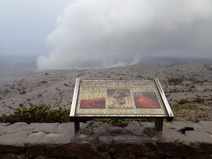 At 7:45 a.m. HST, view of Halema'uma'u crater from the visitor viewing area in front of the Jaggar Muesum, Hawai'i Volcanoes National Park. A light coating of ash on the Park's interpretative sign resulted from ash falling to the ground from explosive events of the past day. Note the contrast of the plume rising from the Overlook vent this morning (background) with the eruption column that erupted during explosive activity in May 1924 (middle photograph on sign). Photo taken Thursday, May 17, 2018 courtesy of U.S. Geological Survey
