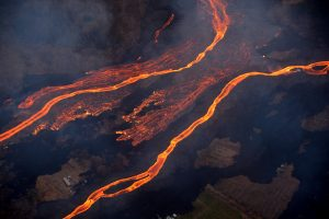 On Wednesday, May 23, the Hilo Civil Air Patrol conducted flights over the lower East Rift Zone eruption to assist USGS and Hawai'i County Civil Defense Agency as they respond to the Kīlauea eruption. This image shows the scale of the lava channels feeding the ocean entries. Note that lava is overflowing the channels and is on top of slightly older, black lava flows. The visible haze is sulfur dioxide gas that's being emitted from the fissures. Photo courtesy of J. Ozbolt, Hilo Civil Air Patrol.