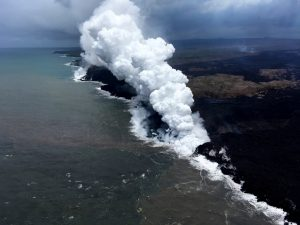 """An aerial view, looking west, of the two active ocean entries on Kīlauea Volcano's lower East Rift Zone. The large white plume (foreground) is the eastern ocean entry; the weaker, western plume can be seen in the distance. The white plume, referred to as """"laze,"""" is a mixture of condensed acidic steam, hydrochloric acid gas, and tiny shards of volcanic glass that can irritate lungs, eyes and skin. Photo taken Saturday, May 26, 2018 courtesy of U.S. Geological Survey"""