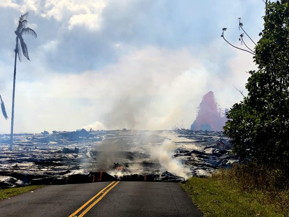 Pāhoehoe lava advancing west from fissure 7 (lava fountain in background) on Leilani Avenue. Fissure 7 activity increased overnight, with lava fountains reaching 50 to 60 m (164 to 197 ft) high. Photo taken Sunday, May 27, 2018 courtesy of U.S. Geological Survey