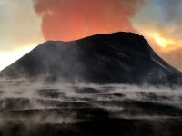 Fissure 8 produces a lava fountain that pulses to heights of 55 to 60 m (185 to 200 ft). Spattering has built a cinder cone that partially encircles fissure 8, now 51 m (170 ft) tall at its highest point. The steam in the foreground is the result of heavy morning rain falling on warm (not hot) tephra (lava fragments). Photo taken Saturday, June 16, 2018 courtesy of U.S. Geological Survey