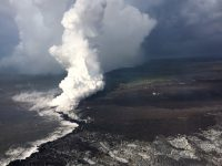 Lava enters the ocean entry in the vicinity of Vacationland, producing a vigorous laze plume. Lava flowing into the ocean has built a delta of flows, rock rubble and black sand, which is over 320 acres in size. Photo taken Sunday, June 17, 2018 courtesy of U.S. Geological Survey