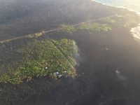 Lava still oozes from the northern edge of the 'a'ā flow near the lighthouse at Cape Kumukahi (upper right). Smoke from burning vegetation marks location of lava oozeouts. View is toward the northeast. Photo taken Sunday, July 8, 2018 courtesy of U.S. Geological Survey