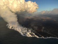 """Multiple ocean entries were active this early morning, each contributing to the prominent """"laze"""" plume above the area. Lava moves from the open channel through the molten core of the broad 'a'ā flow field to the ocean. Kapoho Crater is at middle right of photo. Photo taken Sunday, July 8, 2018 courtesy of U.S. Geological Survey"""