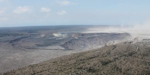 An aerial view of Kīlauea Volcano's summit taken on August 1. A section of Hawai'i Volcanoes National Park's Crater Rim Drive and the road leading to the Kīlauea Overlook parking area are visible at lower right. HVO, Jaggar Museum, and the museum parking area are visible at far middle right. A down-dropped section of the caldera floor can be seen to the left of Halema'uma'u, a crater that continues to grow. On the caldera rim (upper right) light-colored ash deposits from explosions in May are stirred up by brisk winds, creating a dust cloud that's blown downwind. Photo taken Wednesday, August 1, 2018 courtesy of U.S. Geological Survey