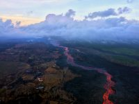 "An early morning aerial view (looking west) of the fissure 8 lava channel. Downstream of the vent, the channel splits to form a ""braided"" section in the lava channel, and, this morning, the north (right) arm of the braided section appeared to be partially abandoned. Lava was still visible in part of the northern braid, but the lower section was only weakly incandescent. During today's overflight, lava within the channel generally appeared to be at a lower level than in previous days. Photo taken Thursday, August 2, 2018 courtesy of U.S. Geological Survey"