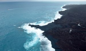 "On July 13, we posted an image of a tiny ""island"" forming just offshore of the Kapoho ocean entry. Today, that feature—likely a submarine tumulus of lava that built up underwater and emerged above sea level—is no longer an ""island."" It now looks more like a peninsula, attached to the coast by a black sand tombolo, a sandy isthmus, creating a feature known as a ""tied island."" Whether or not it will withstand wave erosion over time remains to be seen. Photo taken Thursday, August 2, 2018 courtesy of U.S. Geological Survey"