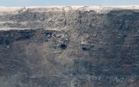 As Halema'uma'u collapsed, older volcanic deposits (layers of ash and lava flows) and features hidden for decades have been revealed in the crater walls, visible here with the aid of a telephoto lens. Photo taken Thursday, August 9, 2018 courtesy of U.S. Geological Survey