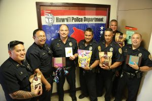 South Hilo Patrol Officers display gifts and a card that were sent to an injured Honolulu Police Officer and his K-9 Hunter