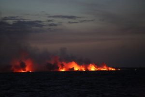 Nighttime scene from shipboard of lava entering the Pacific Ocean on July 12, 2018, captured from a scientific research vessel deploying submarine seismometers. Photograph courtesy of Jackie Caplan-Auerbach, Western Washington University.