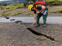 Cracks and sinkholes are measured on Crater Rim Trail at Hawaii Volcanoes National Park. NPS Photo.