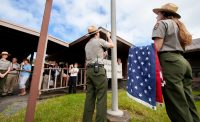 Park Rangers raise the flags outside Kilauea Visitors Center on the first day of Hawaii Volcanoes National Park being reopened after 134-days of closure due to the seismic damage due to Kilauea Volcano's activity. Photography by Baron Sekiya | Hawaii 24/7