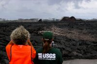 USGS scientists use an Unmanned Aircraft System (UAS, or drone) to fly a MultiGas instrument along Kīlauea Volcano's lower East Rift Zone to determine concentrations of volcanic gases in small plumes rising from the now inactive fissures. The UAS is barely visible in the distance, just to the upper left of fissure 21 (larger cone at right). Photo taken Monday, November 26, 2018 courtesy of U.S. Geological Survey