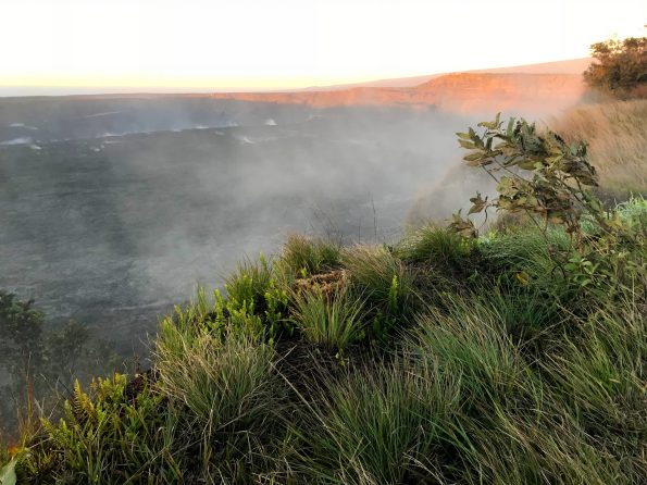 A midwinter dawn at Halemaʻumaʻu on Kīlauea. Steaming cracks tell of water and heat interacting beneath the summit caldera of the volcano. In the background, the first rays of sunlight illuminate Uēkahuna Bluff. USGS photo by E. F. Younger, December 2018.