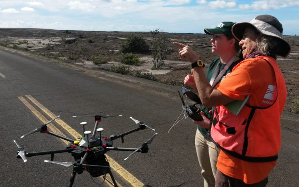 A USGS pilot and Hawaiian Volcano Observatory gas geochemist prepare to conduct a test flight of an unmanned aerial system (UAS) on Kīlauea Volcano in November 2018. This UAS was outfitted with a prototype miniaturized multi-gas sensor for the detection of volcanic gases emitted by Kīlauea, including sulfur dioxide and carbon dioxide. USGS photo by Patricia Nadeau.