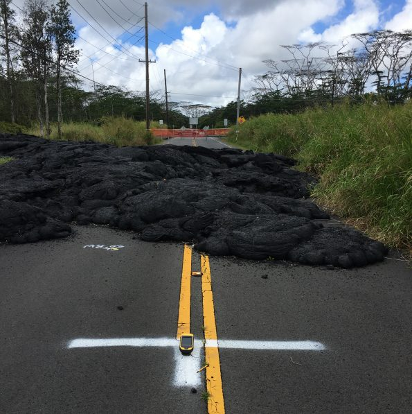 "A high-precision GPS unit (on white ""T"" in foreground) records its position at a ground control point along Pohoiki Road. This marker was painted in July 2018 and is visible in numerous aerial photographs taken by Hawaiian Volcano Observatory geologists throughout Kīlauea's lower East Rift Zone eruption last summer. GPS data are recorded over a period of four minutes at each location, enabling vertical precision of approximately 18 cm (7 in). USGS photo by M. Zoeller, 03/22/2019."