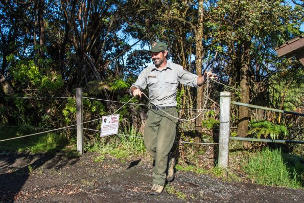 Removing a closure sign at Kilauea Iki. NPS Photo by Janice Wei