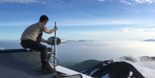 A USGS Hawaiian Volcano Observatory scientist, while assisting Alaska Volcano Observatory colleagues this summer, mounted a radio antenna on an upgraded seismic station at Great Sitkin Volcano in the western Aleutian Islands. USGS photo by A. Darold, 06-20-2019.