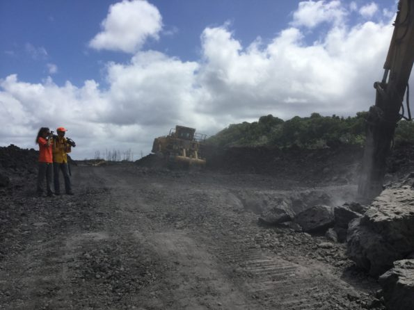 Two HVO geologists document road cutting activities on HWY 132 on August 7, 2019. One geologist is taking visual photographs while another geologist is taking thermal photographs to make a tandem pair for comparison. The temperature of the solidified lava was measured to 425° C (800° F) at the digging site. Photograph by USGS geologist K. Mulliken.