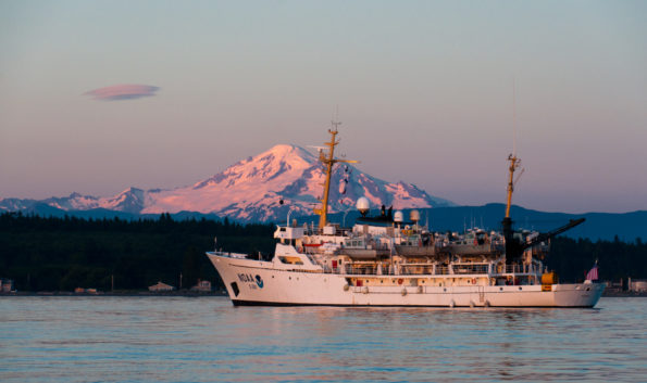 The National Oceanic and Atmospheric Administration Ship Rainier is backdropped by Mount Baker, an active Cascade Range stratovolcano, in Washington. In September 2019, the Rainier conducted a bathymetric survey along Hawaiʻi Island's Puna coast, where lava entered the ocean during Kīlauea Volcano's 2018 eruption. Photo courtesy of NOAA.