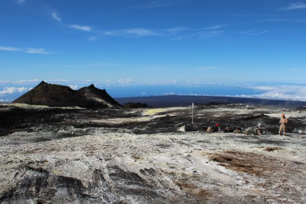Sulphur Cone (left), viewed toward southwest, from 3,480 m (11,420 ft) above sea level on Mauna Loa's southwest rift zone.  At right, an HVO geoscientist and technician rebuild volcanic gas monitoring equipment installed near an outgassing fissure.